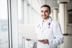 Attractive young medical worker using laptop. Isolated on white background royalty free stock images