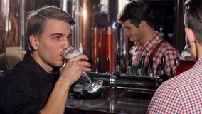 Attractive young man enjoying drinking beer with his friend royalty free stock image