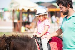 Cute toddler girl riding a horse. Attractive young men helps his cute toddler daughter riding a horse. equestrian sport for kids, little horseman Royalty Free Stock Photography