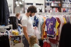 Attractive young father choosing baby clothes. Attractive young men and his cute little daughter at the kids apparel shop, bying clothes together Royalty Free Stock Photography