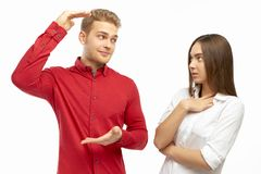 An attractive young man in a red shirt, spreads his hands, showing something huge to his girlfriend stock photography