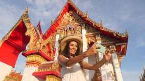 Attractive Young Mixed Race Tourist Girl in White Dress and Big Straw Hat Taking Selfie Photo with Mobile Phone at Thai. Buddhist Temple. Phuket, Thailand. 4K stock footage
