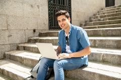 Attractive young modern man working with computer in the city on outside stairs. Young handsome modern man in smart casual wear using laptop computer in the city stock photography