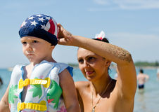 Mother fastening her sons swimming. Attractive young mother fastening her cute little sons swimming cap colours American flag as he readies himself his colourful royalty free stock image