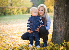 Attractive young mother with her son in the park. Royalty Free Stock Photography