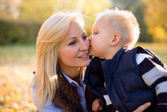 Attractive young mother with her son in the park. Royalty Free Stock Photos