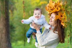Attractive young mother holding baby girl in forest Stock Image