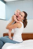 Attractive young mother holding cute baby in bedroom. Portrait of an attractive young mother holding cute baby in bedroom Stock Photography