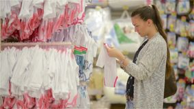 Attractive young mother shopping for childrens clothes in a retail clothing store viewing items on a rack, beautiful
