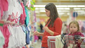 Attractive young mother shopping for childrens clothes in a retail clothing store viewing items on a rack, beautiful stock video