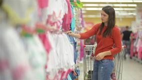 Attractive young mother shopping for childrens clothes in a retail clothing store viewing items on a rack, beautiful stock footage