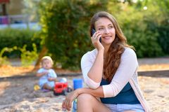 Attractive young mother talking on her mobile royalty free stock image