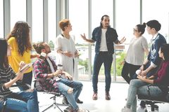 Attractive young multiethnic group talking at relax zone in coffee break time at office. Young asian hipster man sharing lifestyle stock photos