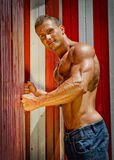 Attractive young muscle man leaning against colorful beach changing rooms Royalty Free Stock Photography