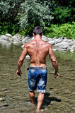 Attractive young muscleman walking in water pond seen from the back Stock Photos