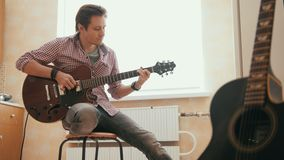 Attractive young musician composes music on the guitar and plays, other musical instrument in the foreground. Attractive young musician composes music on the stock video