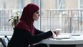 Attractive young muslim girl with hijab uses laptop to find some important information.  stock video
