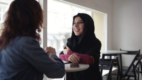 Attractive young muslim woman in black hijab is talking to her female caucasian friend while sitting in Coffee Shop. Women smiling, laptop and smartphone on stock video