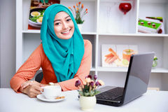 Attractive young muslim woman enjoying a cup of tea while using Royalty Free Stock Photography