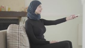 Beautiful successful confident young muslim woman using the remote to turn on the TV wearing traditional headscarf on stock video footage