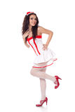 Attractive young nurse. Full body shot of a sexy beautiful young nurse wearing red high heels shoes touching herself and smiling on isolated white background Royalty Free Stock Images