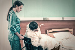 Attractive young nurse in uniform pulling wheelchair with ill pa Royalty Free Stock Photo