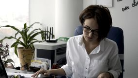 Attractive young office woman in white shirt working on the business papers near green plant and printer. Female office royalty free stock photo