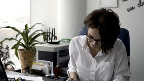 Attractive young office woman in white shirt working on the business papers, signing documents near green plant and royalty free stock photography