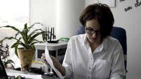 Attractive young office woman in white shirt working on the business papers, signing documents near green plant and stock photos