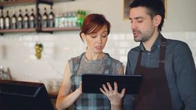 Attractive young people coffee house owners are using tablet and talking while working at counter. Partnership. Attractive young people coffee house owners are stock footage