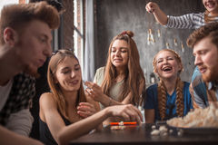 Attractive young people throwing popcorn and enjoying together. Stock Images