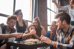 Attractive young people throwing popcorn and enjoying together. Royalty Free Stock Images