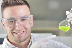 Attractive young PhD student scientist observing the color shift after the solution destillation in chemical laboratory Stock Photo