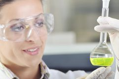 Attractive young PhD student scientist observing the color shift after the solution destillation in chemical laboratory Royalty Free Stock Photography
