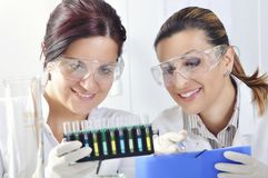 Attractive young PhD students scientists observing the color shift after the solution destillation in chemical laboratory Stock Image