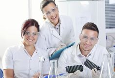 Attractive young PhD students scientists observing the color shift after the solution destillation in chemical laboratory Royalty Free Stock Images