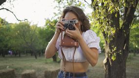 Attractive young photographer with curly hair looking at the camera while taking photo using old camera in the garden or. Attractive young photographer with stock video