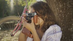 Attractive young photographer with curly hair sitting under the tree taking photo using old camera in the garden or park. Her bicycle standing behind. Rural stock video