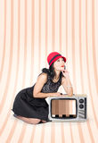 Attractive young pin-up lady on television. Beautiful young woman in studio thinking on old fashion tv in classic clothes signifying retro pinup style Royalty Free Stock Image