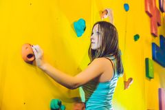 Attractive young professional sport climber woman having trainin. G in the gym at artificial wall Royalty Free Stock Image