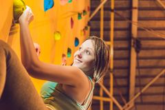 Attractive young professional sport climber woman having trainin. G in the gym at artificial wall Stock Images