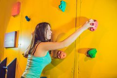 Attractive young professional sport climber woman having trainin. G in the gym at artificial wall Stock Photo