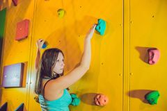 Attractive young professional sport climber woman having trainin. G in the gym at artificial wall Royalty Free Stock Photos