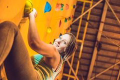 Attractive young professional sport climber woman having trainin. G in the gym at artificial wall Stock Photos