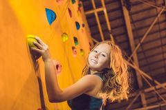 Attractive young professional sport climber woman having trainin. G in the gym at artificial wall Royalty Free Stock Images
