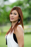 Attractive young redhead Asian woman. In trendy summer clothing posing in front of a green outdoors looking at the camera with a friendly smile Stock Images