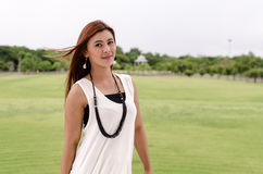 Attractive young redhead Asian woman. In trendy summer clothing posing in front of a green outdoors looking at the camera with a friendly smile Stock Photos