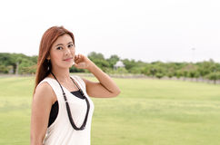 Attractive young redhead Asian woman. In trendy summer clothing posing in front of a green outdoors looking at the camera with a friendly smile Royalty Free Stock Photo