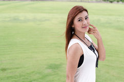 Attractive young redhead Asian. Woman in trendy summer clothing posing in front of a green outdoors looking at the camera with a friendly smile Royalty Free Stock Photography