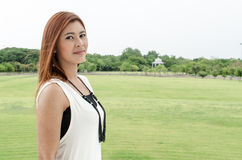 Attractive young redhead Asian woman. In trendy summer clothing posing in front of a green outdoors looking at the camera with a friendly smile Royalty Free Stock Image